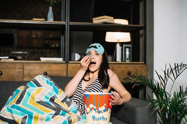 Peur jeune femme assise sur le lit avec du pop-corn