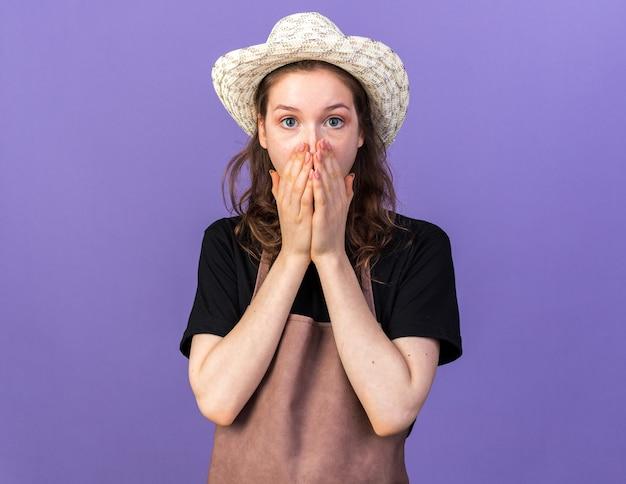 Peur jeune femme jardinier portant chapeau de jardinage visage couvert isolé sur mur bleu