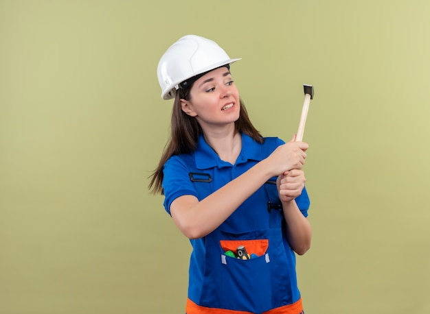 Peur jeune fille constructeur avec casque de sécurité blanc et uniforme bleu détient un marteau avec les deux mains sur fond vert isolé