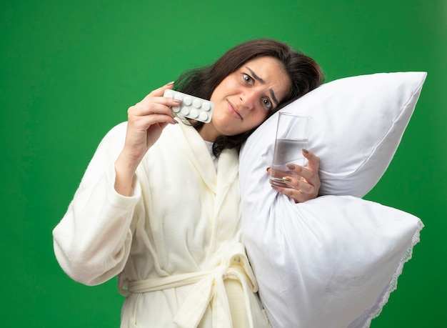 Peur de jeune fille malade caucasienne portant robe hugging oreiller mettant la tête dessus tenant un verre d'eau et montrant pack de comprimés médicaux regardant la caméra isolée sur fond vert
