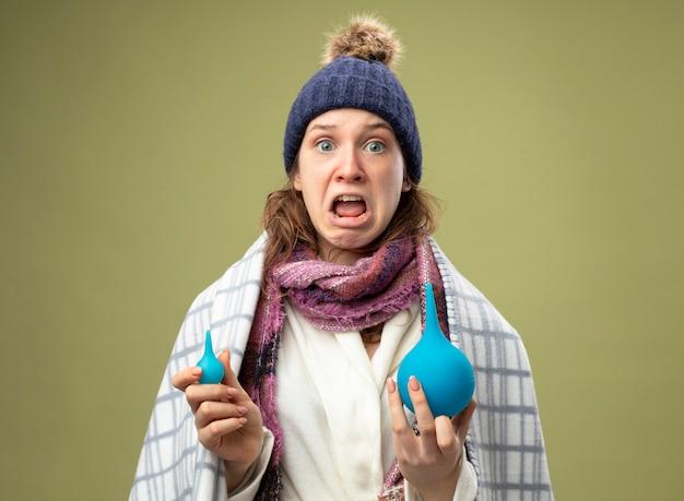 Peur de jeune fille malade portant une robe blanche et un chapeau d'hiver avec un foulard enveloppé dans un plaid tenant des lavements isolés sur vert olive