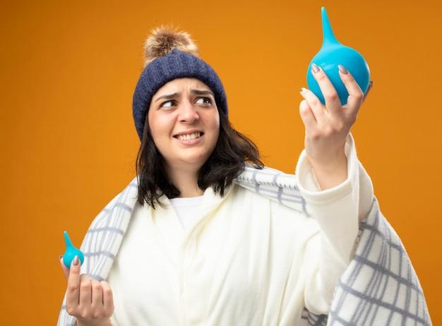 Peur de jeune fille malade de race blanche portant chapeau d'hiver robe enveloppé dans un plaid tenant des lavements soulevant un grand en le regardant isolé sur fond orange