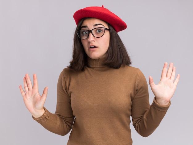 Peur jeune jolie fille caucasienne avec chapeau de béret et lunettes optiques debout avec les mains surélevées