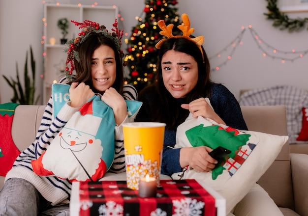 Peur de jolies jeunes filles avec couronne de houx et serre-tête de renne tenir des oreillers et regarder la télévision assis sur des fauteuils le temps de noël à la maison