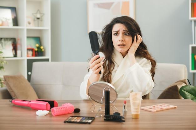 Peur de mettre la main sur la tête d'une jeune fille tenant et regardant un peigne assis à table avec des outils de maquillage dans le salon