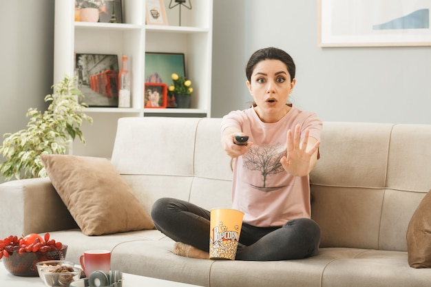 Peur montrant un geste d'arrêt jeune fille tenant une télécommande de télévision, assise sur un canapé derrière une table basse dans le salon