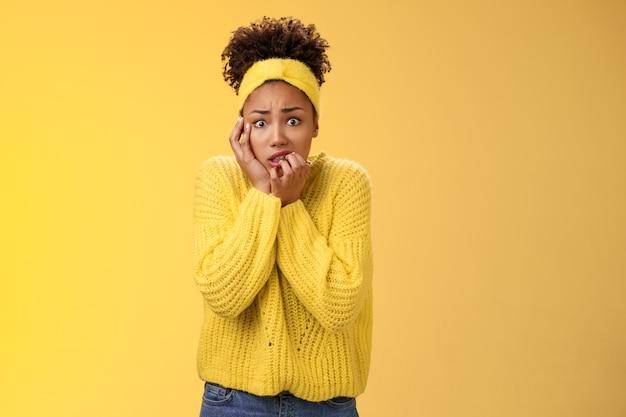 Peur préoccupée nerveuse jeune employée afro-américaine inquiète anxieuse d'être virée serrer les dents se baissant toucher le visage peu sûr des doigts debout effrayé terrifié, fond jaune.