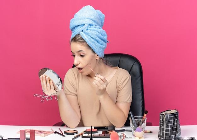Peur en regardant miroir jeune belle fille assise à table avec des outils de maquillage cheveux enveloppés dans une serviette appliquant un brillant à lèvres isolé sur fond rose