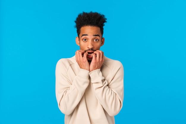 Peur timide et alarmé jeune homme afro-américain tremblant se sentant terrifié, regardant un film d'horreur, se mordant les doigts