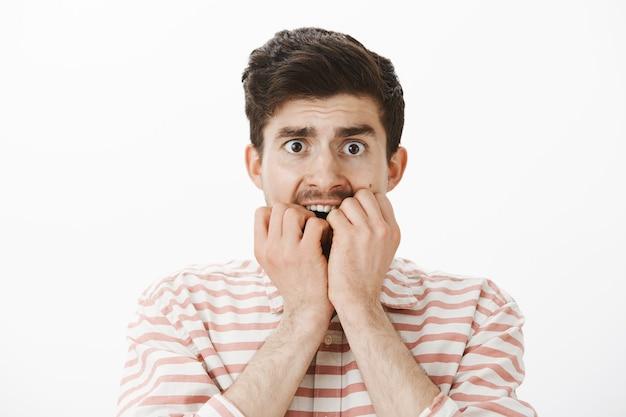 Peur tremblant pauvre gars européen en chemise à rayures, se mordant les doigts et regardant effrayé, ayant peur à mort, regardant un film effrayant seul dans l'obscurité, debout sur un mur gris