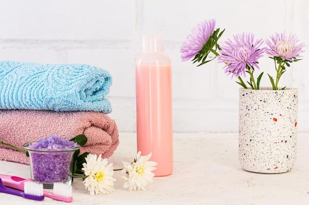 Peut avec du sel de mer, des brosses à dents, une bouteille de shampoing, des serviettes et des fleurs d'asters sur fond blanc. cosmétiques femme et accessoires de lavage.