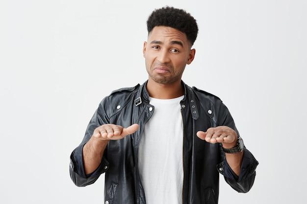 Peut-être que tu te détends, mec. calmez-vous. portrait d'étudiant mâle drôle à la peau foncée mature avec une coiffure afro dans des vêtements élégants décontractés gesticulant avec les mains, regardant à huis clos avec une expression cynique.