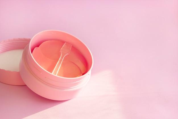 Peut hydrogel cache-œil cosmétique pour les soins de la peau sur fond rose.