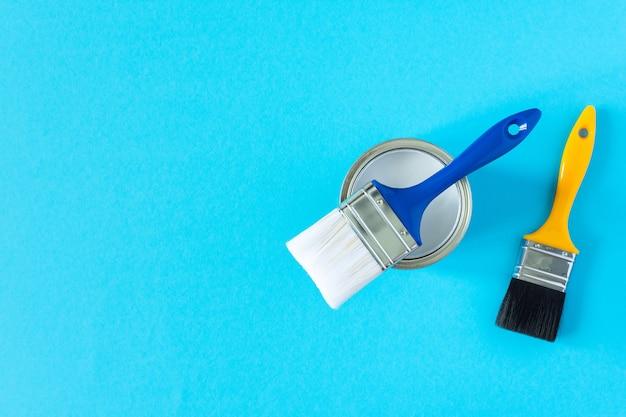 Peut de peinture blanche avec des pinceaux sur fond bleu, peinture, vue de dessus