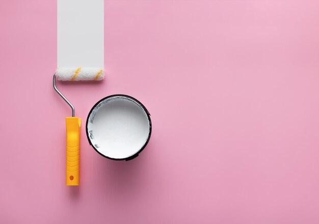 Peut de peinture blanche et rouleau avec bande blanche de peinture sur fond rose avec espace de copie.