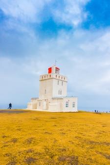 Phare blanc à cape dyrholaey, en islande. .