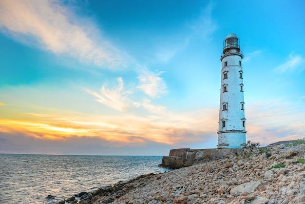 Phare sur la côte de la mer avec ciel coucher de soleil