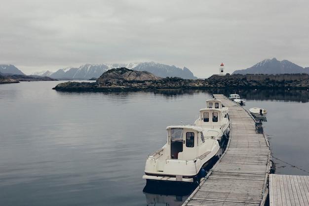 Phare dans les eaux sauvages et lointaines de l'atlantique mer du nord, entre les rochers d'un port nordique.