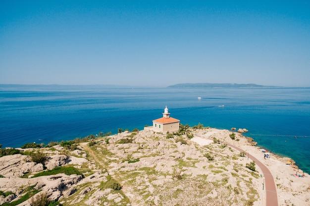 Le phare en pierre blanche s'est installé sur la côte en mer adriatique cle