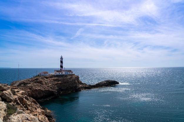 Phare sur la pointe d'un sol rocheux entrant dans la mer par une journée ensoleillée