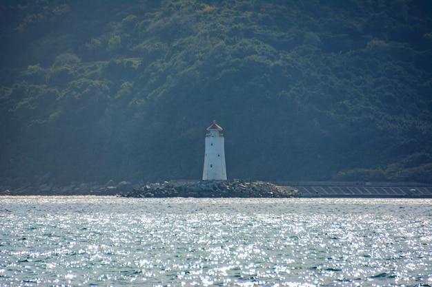 Un phare solitaire est vu dans le brouillard sur fond de forêt tropicale, de montagnes et de mer turquoise sur la côte de la baie de yalong en mer de chine méridionale. sanya, île de hainan, chine. paysage naturel.