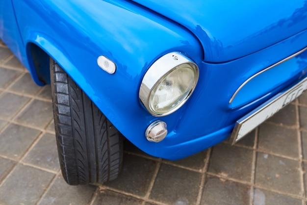 Le phare d'une vieille petite voiture
