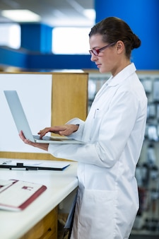 Pharmacien à l'aide d'un ordinateur portable en pharmacie
