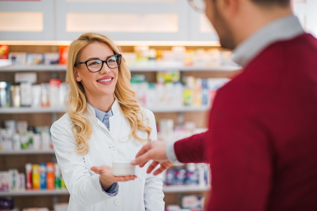 Pharmacien et client dans une pharmacie.