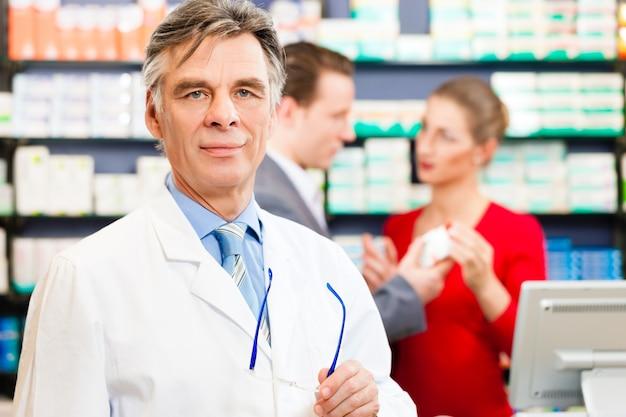Pharmacien avec des clients en pharmacie