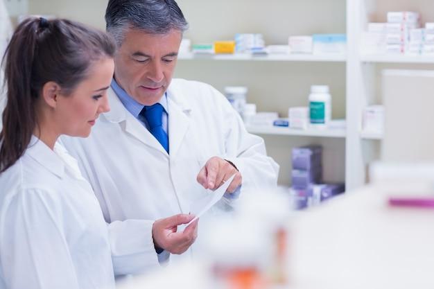 Pharmacien expliquant une prescription à son stagiaire
