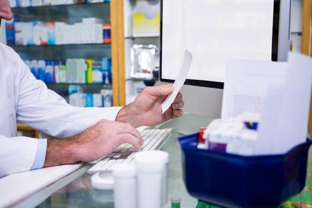 Pharmacien faisant des entrées sur ordinateur