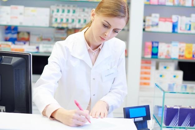 Pharmacien féminin faisant des devoirs quotidiens