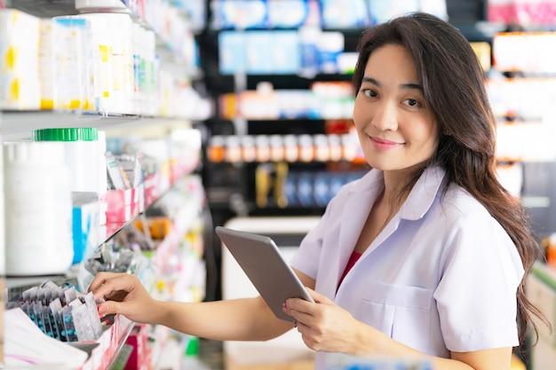 Pharmacien femme prenant un médicament sur l'étagère et utilise une tablette numérique à la pharmacie