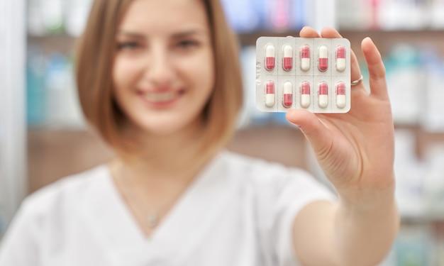 Pharmacien montrant blister avec des pilules.