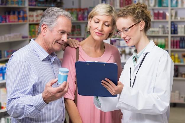 Pharmacien montrant le presse-papiers aux clients