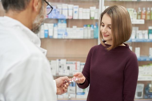 Pharmacien offrant un blister de pilules au client.