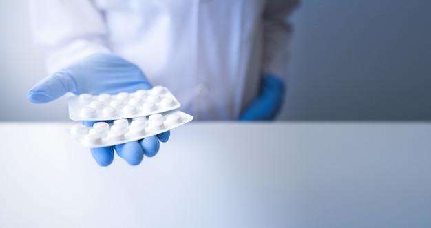 Pharmacien offrant blister de pilules blanches sur fond blanc et gants bleus