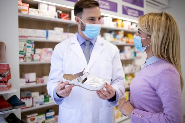 Le pharmacien parle au client et lui recommande les chaussures à acheter.