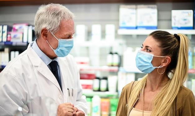 Pharmacien principal traitant avec un client, tous deux portant des masques en raison d'un coronavirus