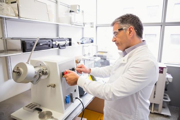 Pharmacien senior utilisant une machine pour fabriquer des médicaments