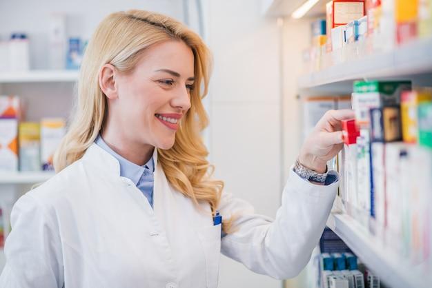 Pharmacien souriant prenant des médicaments sur une étagère, gros plan.