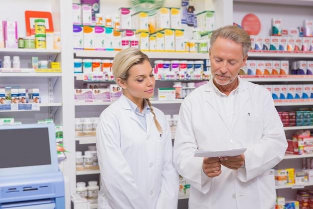 Pharmacien et stagiaire discutant de la prescription
