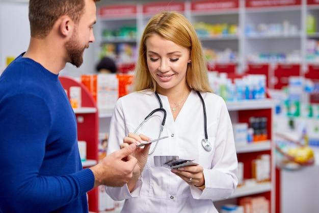 Un pharmacien sympathique caucasien a une belle conversation avec un client