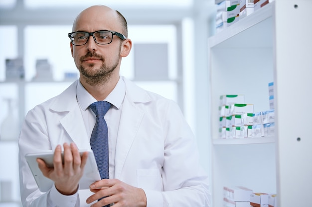 Pharmacien avec une tablette numérique debout dans sa pharmacie