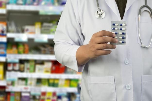 Pharmacien tenant le blister sur le magasin