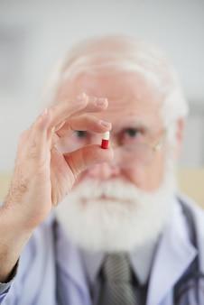 Pharmacien tenant une capsule