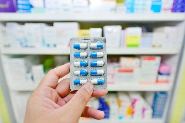 Pharmacien tenant un paquet de capsules de médicaments à la pharmacie