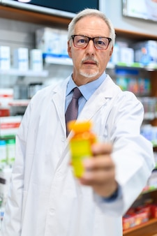 Pharmacien tenant un pot de pilules
