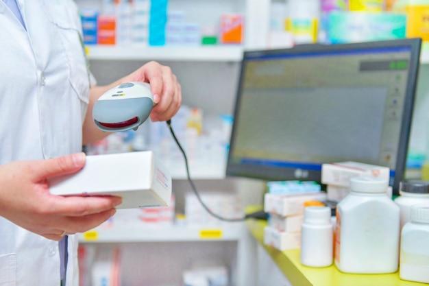 Pharmacien en train de scanner un code-barres d'un médicament dans une pharmacie.