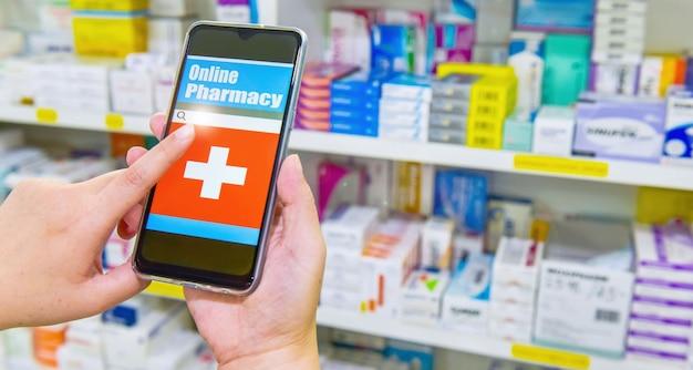 Pharmacien utilisant un téléphone intelligent mobile pour la barre de recherche sur l'affichage dans les étagères des pharmacies